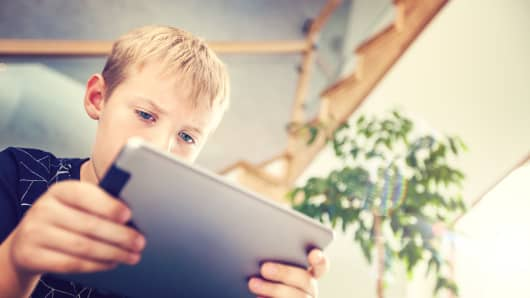Schoolboy with  digital tablet sitting and reads