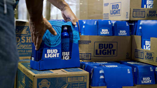 An employee adjusts bottles of Bud Light brand beer at an Anheuser-Busch InBev NV facility in Williamsburg, Virginia, U.S., on Wednesday, Aug. 8, 2018.