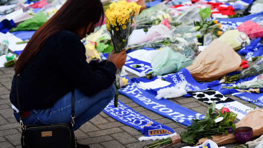 A woman pauses as she adds flowers to a growing pile of tributes outside Leicester City Football Club's King Power Stadium in Leicester, eastern England, on October 28, 2018 after a helicopter crash killed the club's Thai chairman Vichai Srivaddhanaprabha and four others on board.