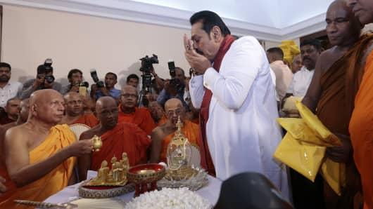 Sri Lanka's former president Mahinda Rajapaksa receives blessings from Buddhist monks before assuming duties as the new Prime Minister in Colombo on Oct 29, 2018.