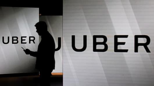 A man checks his smartphone while standing among illuminated screens bearing the Uber logo.