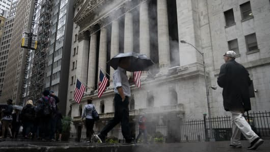 People walk past the New York Stock Exchange (NYSE) on a rainy day in the Financial District, October 11, 2018 in New York City.