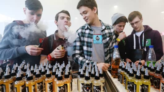 Teenage visitors smoking electronic cigarettes at a vape trade fair.