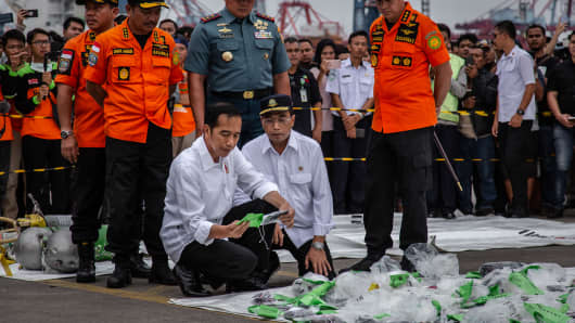 Indonesia's President Joko Widodo holds a personal item from Lion Air flight JT 610 at the Tanjung Priok port on October 30, 2018 in Jakarta, Indonesia.