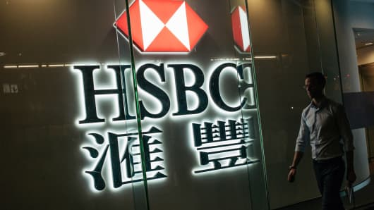 A pedestrian walks past illuminated signage for HSBC Holdings Plc displayed outside a bank branch in the Central district of Hong Kong, China.