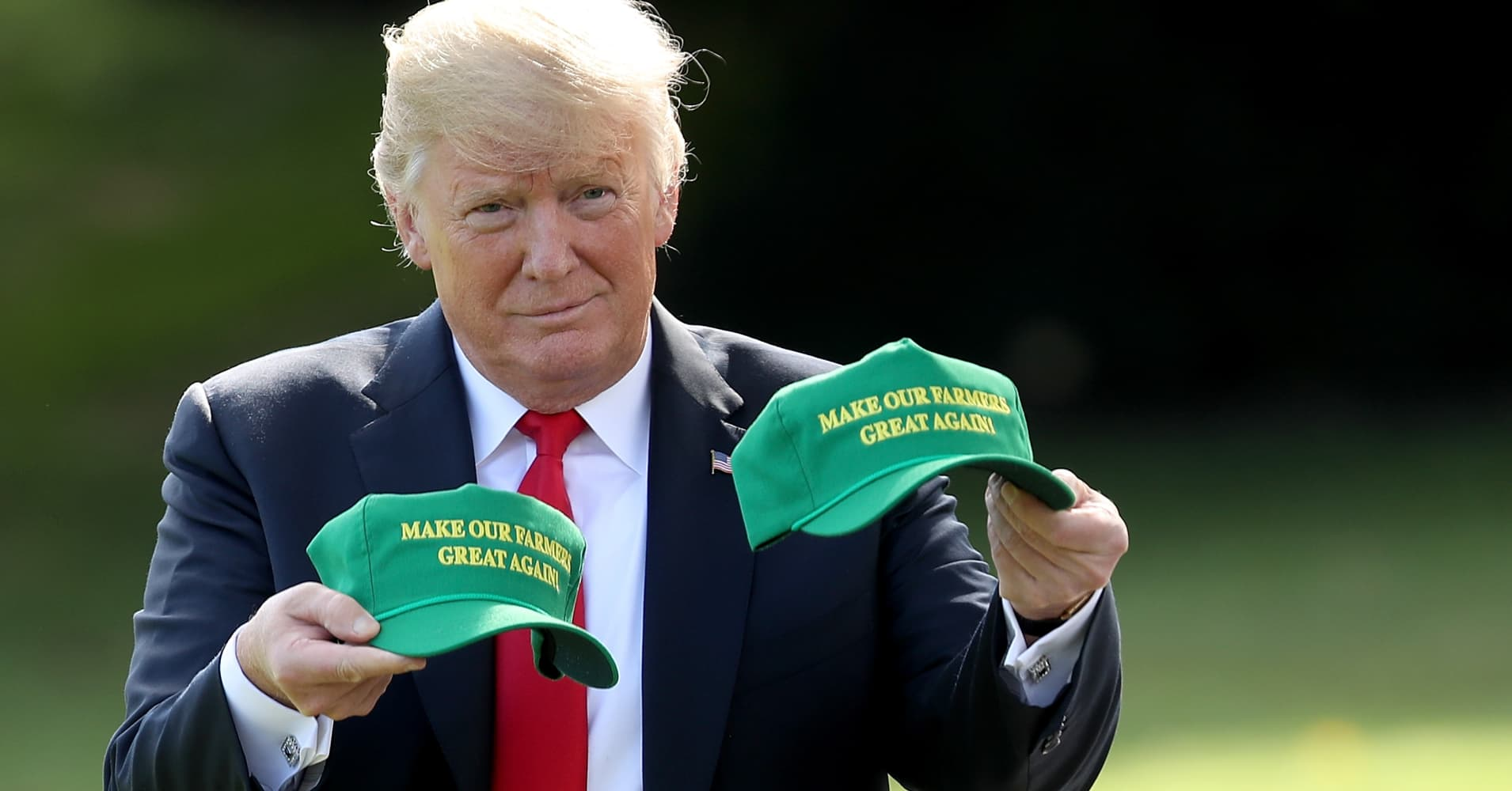 President Donald Trump holds up two hats that say 'Make Our Farmers Great Again' as he departs the White House August 30, 2018 in Washington, DC.