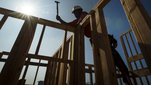 A contractor uses a hammer while working on townhouse under construction at the PulteGroup Metro housing development in Milpitas, California, Oct. 25, 2018.