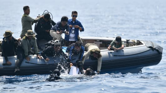 Indonesian Navy divers try to put a 'black box' into a plastic container after its discovery during search operations for the ill-fated Lion Air flight JT 610 at sea, north of Karawang in West Java on November 1, 2018.