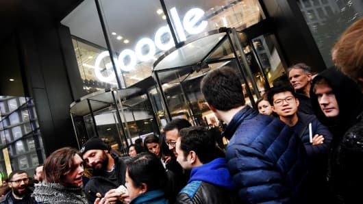 Workers stand outside the Google offices after walking out as part of a global protest over workplace issues, in London, Britain, November 1, 2018.