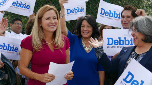 Surrounded by a small group of family and supporters, Democrat Debbie Mucarsel-Powell, left, announces she is running against Republican U.S. Rep. Carlos Curbelo,  outside the West Perrine Health Center in Miami on Wednesday, Aug. 2, 2017.