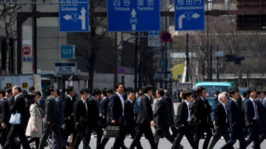 White-collar workers walk on a crosswalk in Tokyo on April 3, 2017.