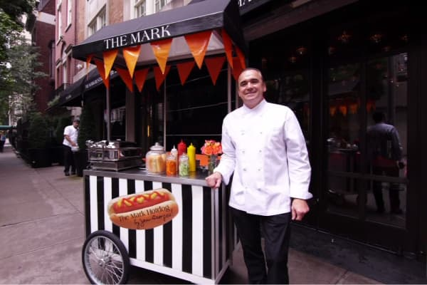 Chef Jean-Georges Vongerichten stands next to his gourmet hot dog cart outside the Mark Hotel in New York City.