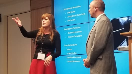 Rebecca Morgan, a volunteer with Operation Safe Escape, discusses counter-surveillance and domestic violence safe houses with Christopher Cox, a founder of the organization, at an October conference in Washington D.C.