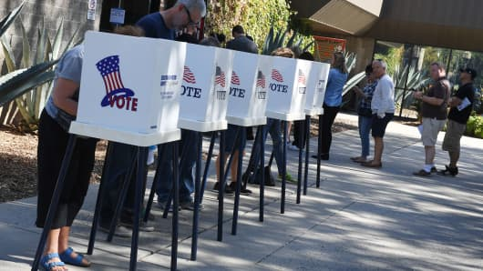 People vote at outdoor booths during early voting for the mid-term elections in Pasadena, California on November 3, 2018.