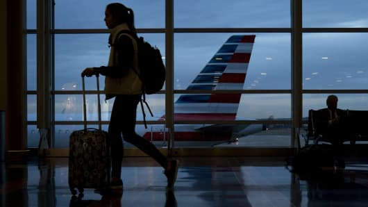 A traveler walks past an American Airlines Group Inc. aircraft at Ronald Reagan National Airport (DCA) in Washington, D.C.
