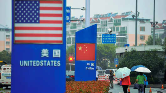 Signs with the US flag and Chinese flag are seen outside a store selling foreign goods in Qingdao in China's eastern Shandong province on Sept. 19, 2018.