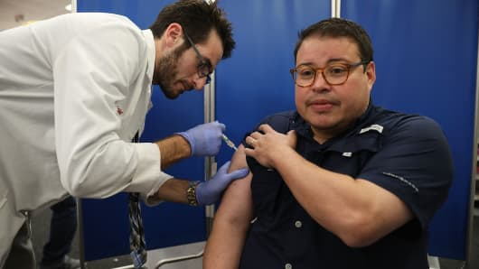 Mario Ancalmo receives an influenza vaccination from Raphael Lynne, Pharm. D., MBA, at the CVS/pharmacy on October 4, 2018 in Miami, Florida.