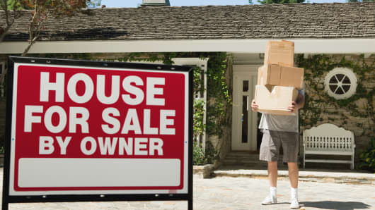 Mature man carrying boxes to move into newly bought property