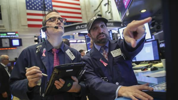 Traders and financial professionals work on the floor of the New York Stock Exchange (NYSE) at the opening bell, October 25, 2018 in New York City.