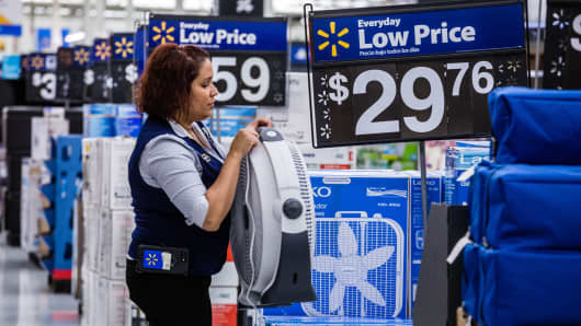 An employee arranges a fan on display for sale at a Walmart store in Secaucus, New Jersey.