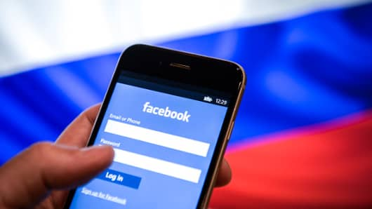 An iPhone with a Facebook logo is seen with a Russian flag in the background in this photo illustration.