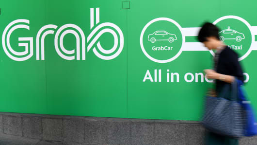 A woman walks past the Grab transport office in Singapore on September 24, 2018.