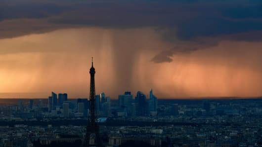 A picture taken on May 30, 2018 from the observatory deck of the Montparnasse tower in Paris shows the Eiffel Tower in Paris and La Defense business district under heavy clouds at sunset.