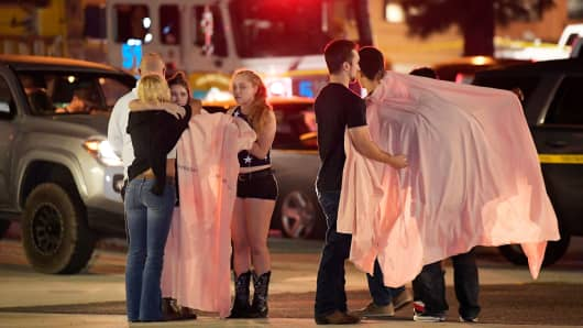 "People comfort each other as they stand near the scene Thursday, Nov. 8, 2018, in Thousand Oaks, Calif. where a gunman opened fire Wednesday inside a country dance bar crowded with hundreds of people on ""college night."""