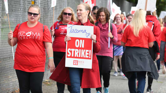 Teachers and supporters march while holding signs during a strike outside the Jason Lee Middle School in Tacoma, Washington, on Wednesday, Sept. 12, 2018.