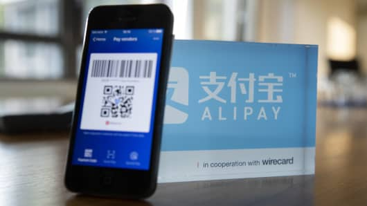 An Alipay digital payment app logo and smartphone sit on a desktop at the Wirecard AG headquarters in Munich, Germany, on Wednesday, Sept. 5, 2018.