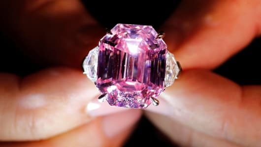 A Christie's staff holds a 18.96 carat Fancy Vivid Pink Diamond during a preview in Geneva, November 8, 2018.