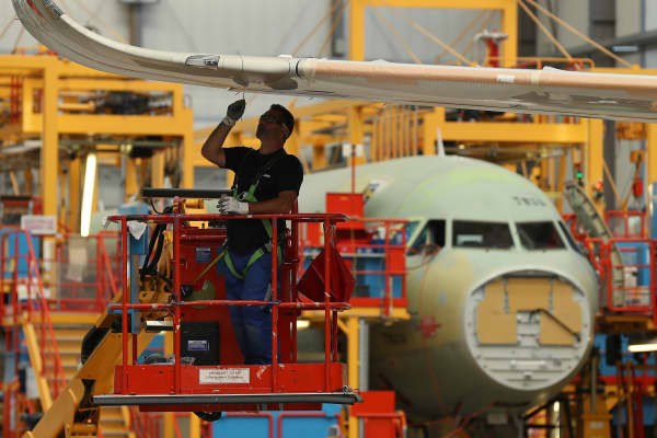 A worker fits a part to a wing of a partially-finished passenger plane of the A320 series in an assembly hall.