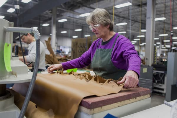 A worker uses a die-cutting machine to cut out shapes of leather to be sewn into boots at the L.L. Bean manufacturing facility in Brunswick, Maine.