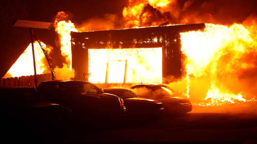 An used car dealership is seen engulfed in flames during the Camp Fire in Paradise, California, November 8, 2018.