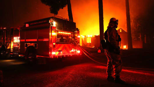 Firefighters try to save a building as the Camp Fire moves through the area on November 8, 2018 in Paradise, California.