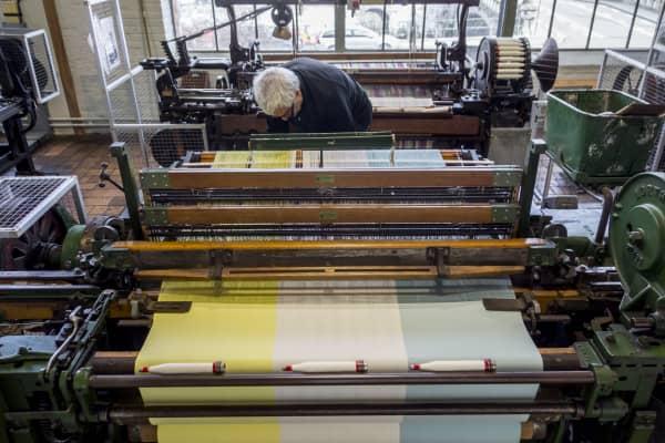 Fabric weaver operating mechanical flying shuttle loom.