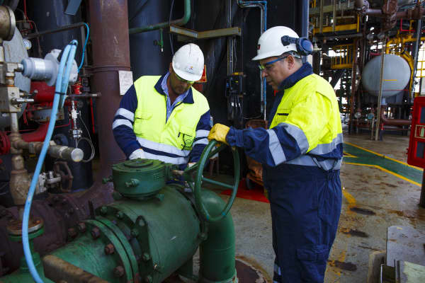Engineers check pipe valves on the towel deck aboard an oil platform.