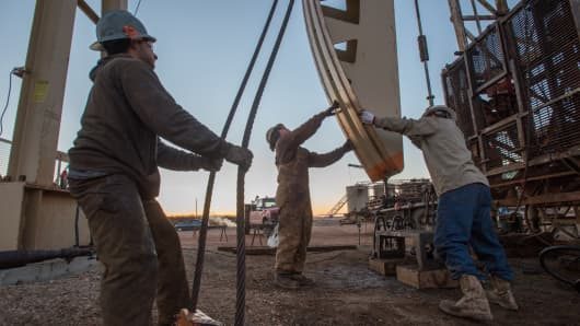Oil field workers tend to a pump jack.