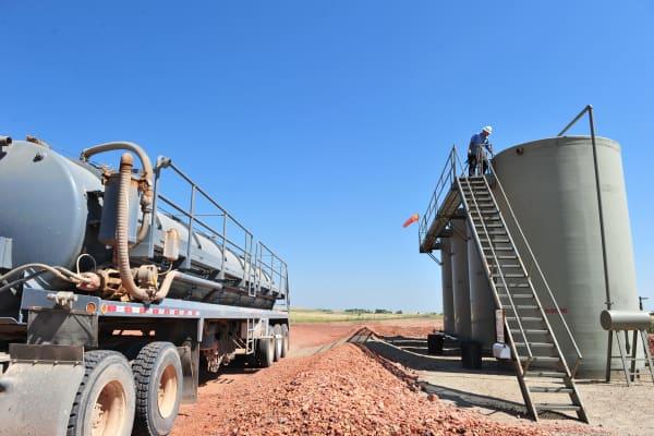 A worker checks on oil tanks at an oil well near Tioga, North Dakota.