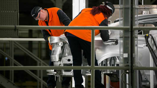 Workers inspect a vehicle body during production of a sedan.