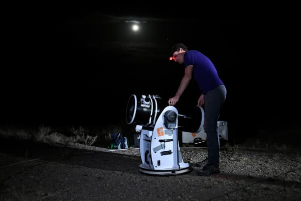 An astronomer sets up a telescope to watch a 'blood moon' eclipse.