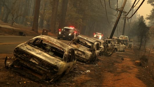 A line of burned out abandoned cars sit on the road after the Camp Fire moved through the area on November 9, 2018 in Paradise, California. Fueled by high winds and low humidity, the rapidly spreading Camp Fire ripped through the town of Paradise and has quickly charred 70,000 acres and has destroyed numerous homes and businesses in a matter of hours.