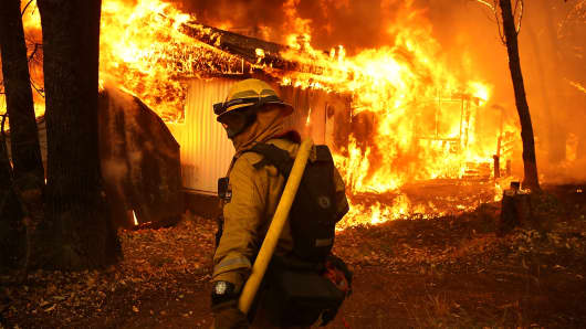 A Cal Fire firefighter monitors a burning home as the Camp Fire moves through the area on November 9, 2018 in Magalia, California.