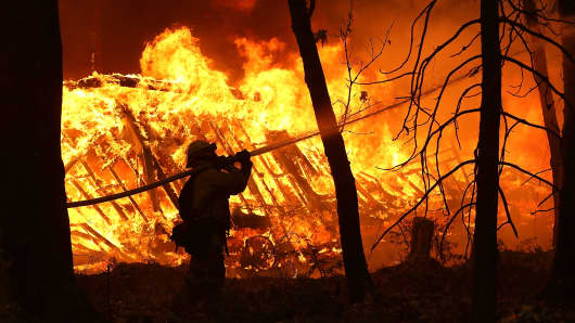 A Cal Fire firefighter sprays water on a home next to a burning home as the Camp Fire moves through the area on Nov. 9, 2018 in Magalia, California.