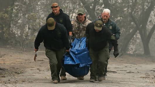 Yuba and Butte County sherriff deputies carry a body bag with a deceased victim of the Camp Fire on November 10, 2018 in Paradise, California.