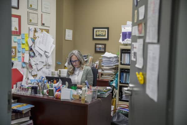 Female college professor working at laptop in messy office