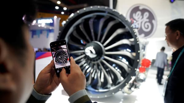 A man takes a picture of a General Electric (GE) engine during the China International Import Expo (CIIE), at the National Exhibition and Convention Center in Shanghai, China November 6, 2018.
