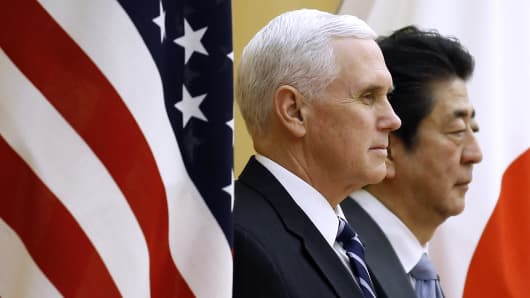U.S. vice president Mike Pence, (L), and Japan's prime minister Shinzo Abe (R), stand between their respective national flags as they review an honor guard ahead of a meeting at the prime minister's official residence in Tokyo, Japan, on Wednesday, Feb. 7, 2018.