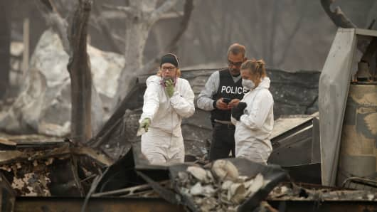 Archaeology students from the University of Nevada, Reno's Human Identification Laboratory, help search for victims of the Camp Fire with a county law enforcement officer on Sunday, November 11, 2018, in a mobile home park in Paradise, Calif.