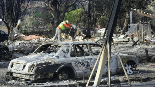Workers check for gas lines amid the damaged homes from the Woolsey Fire on Filaree Heights Road in Malibu, California on November 13, 2018.